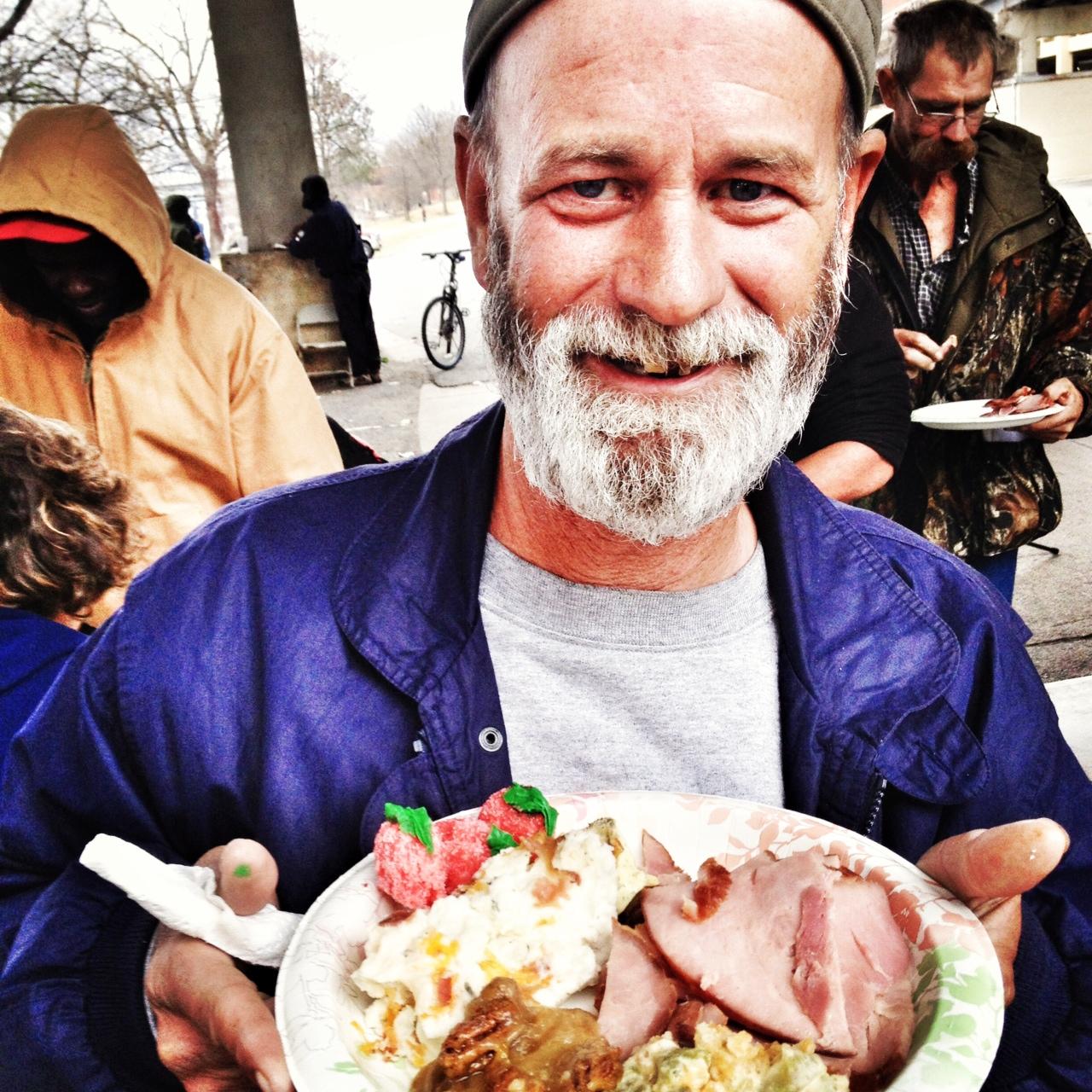 homeless man with plate of christmas dinner, under the bridge, feeding the homeless